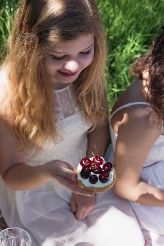 A girl wearing a white summer dress holding a fresh cherry tartlet