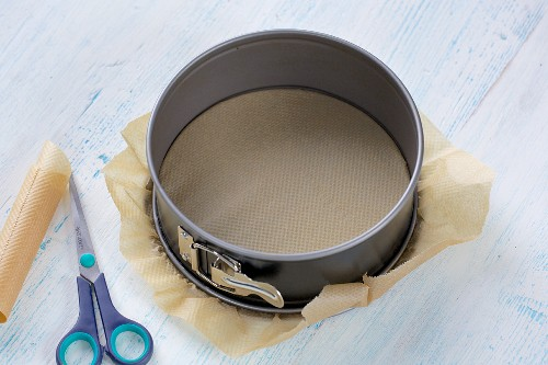 A small springform pan being lined with baking paper