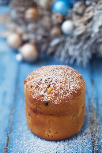 A mini panettone on a blue wooden surface
