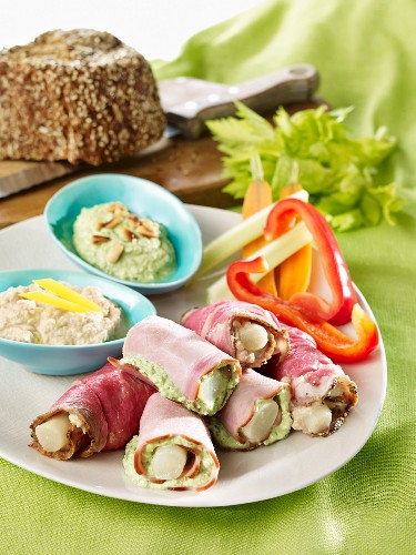 A supper plate featuring black salsify rolls, raw pepper and dips