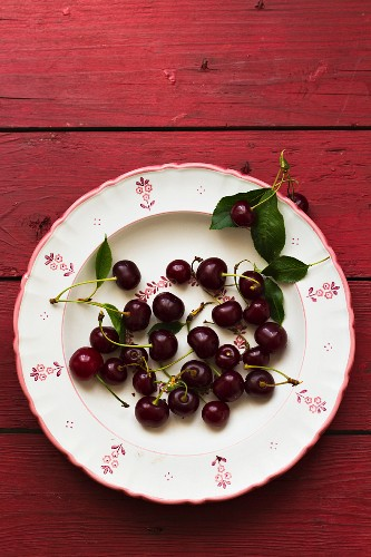 Cherries with leaves on a floral-patterned plates (seen from above)