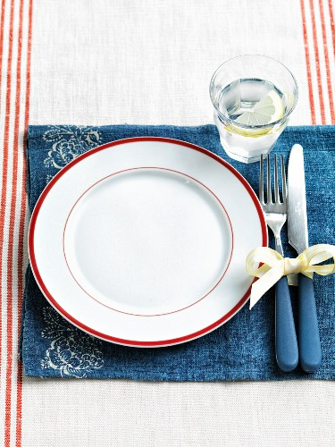 An empty white plate with a red rim on a blue placemat in the glass of water