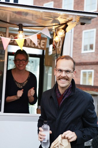 A happy man in front of a mobile food unit holding a bottle of water and a sandwich in a paper bag with a smiling sales assistant in the background