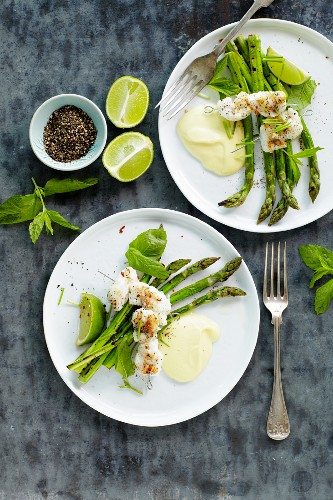 Fish skewers on a bed of green asparagus with a lime sauce