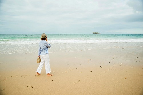 A woman on the phone walking along the beach (Camaret-sur-Mer, France)