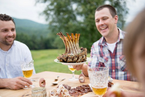 Young men eating outside with a juicy pork crown