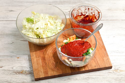 Sliced vegetables with chilli past and salted Chinese cabbage on a chopping board (ingredients for kimchi)