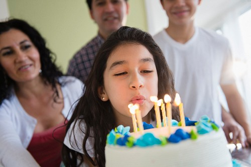 A girl with a birthday cake blowing out candles