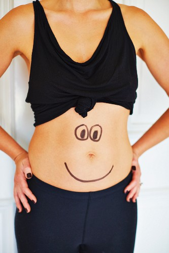 A woman with a face drawn on her tummy