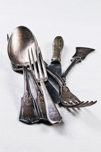 Old silver cutlery on a white table cloth
