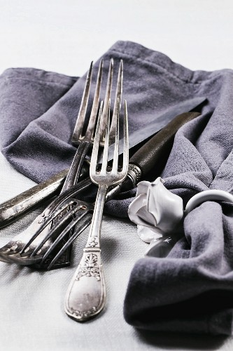 Old silver cutlery with a grey napkin on a white table cloth