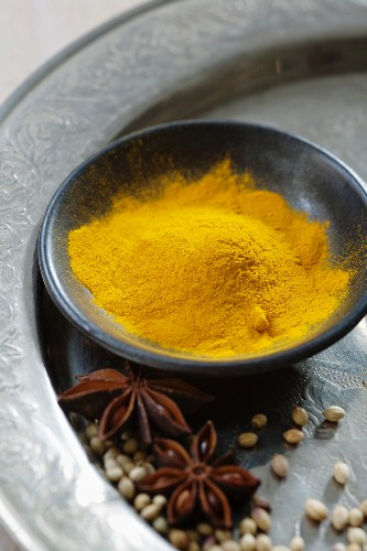 Turmeric powder in a black bowl with star anise and coriander on a silver plate