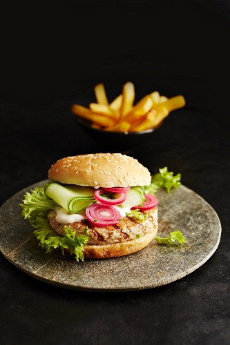A chicken burger and chips on a black surface