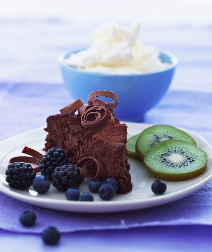 A slice of chocolate cake with fruit on a plate with a bowl of whipped cream in the background