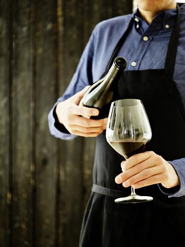 Sommelier hat Rotwein in ein Glas eingeschenkt