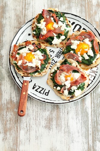 Mini tortilla pizzas with spinach, ham, egg and feta cheese