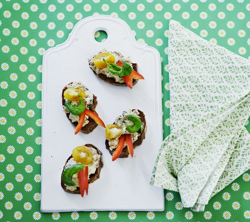 Wholemeal canapés with tuna cream, tomatoes, peppers and basil