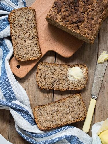 Vollkornbrot mit Leinsamen und Sonnenblumenkernen, eine Brotscheibe mit Butter bestrichen