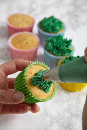 Easter cupcakes being made: green frosting being piped on
