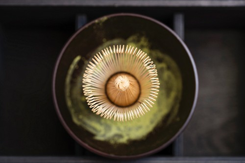A matcha whisk in a matcha bowl with matcha powder (seen from above)