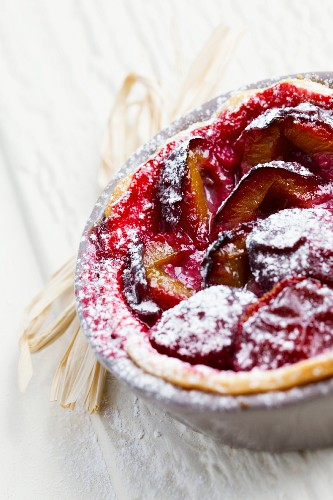 Plum tartlet with icing sugar in a baking dish (close-up)