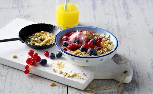Spelt muesli with fresh berry and soy yoghurt, wheat germ and roasted pine nuts