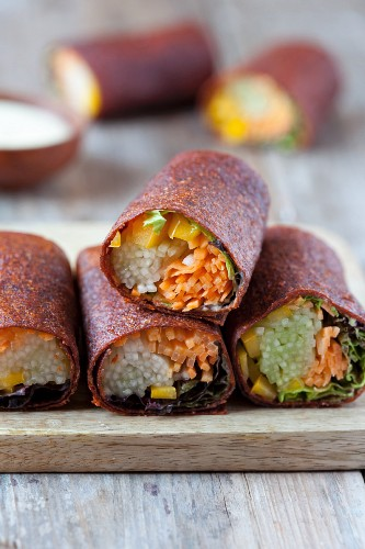 Vegetable-filled wraps on a chopping board