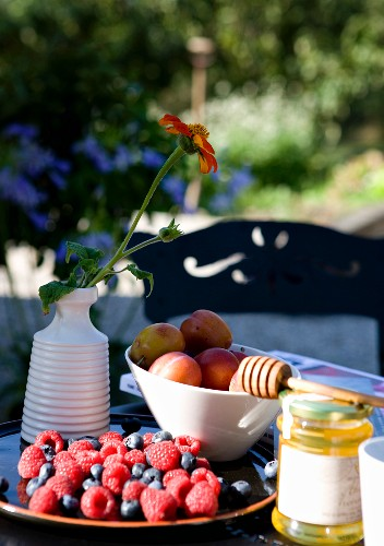 Bowls of fresh berries and plums and flower in ceramic vase on table outdoors