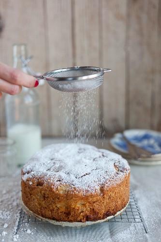 Einen Apfel-Haselnuss-Kuchen mit Puderzucker bestauben