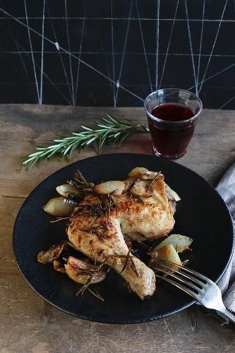 Hähnchenkeule mit Zwiebeln und Rosmarin, dazu ein Glas Rotwein