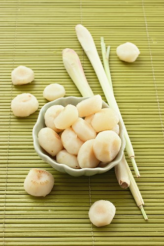 Water chestnuts and lemongrass on a green bamboo mat