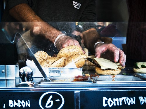 A cheeseburger being prepared in a food truck