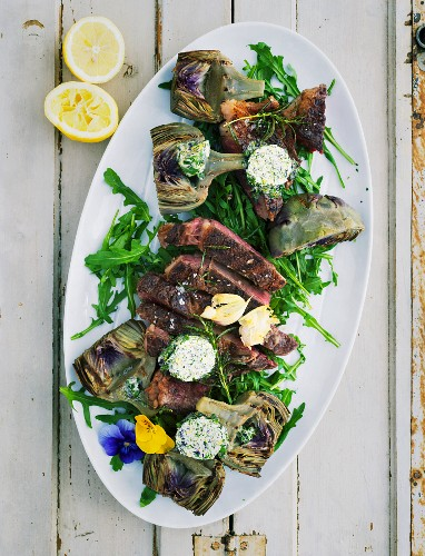 Grilled artichokes with herb and flower butter and a T-bone steak