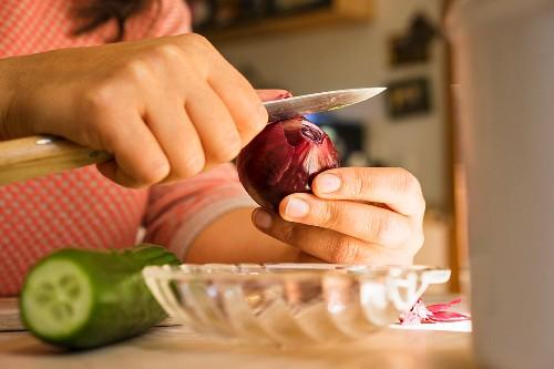 A woman peeling a red onion