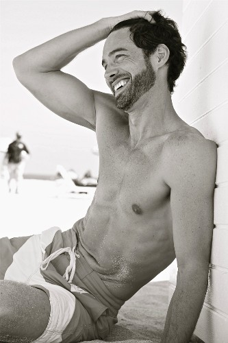 A laughing young man sitting on a beach wearing swimming shorts (black-and-white shot)