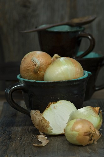 Large sweet onions in a jug, whole and sliced