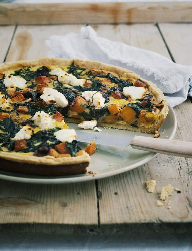 Chard quiche on a wooden board with a knife and a napkin