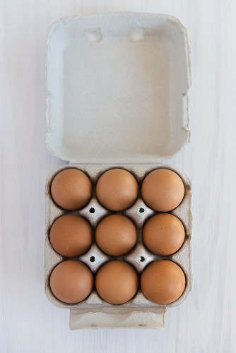 Nine brown eggs in a egg box (seen from above)