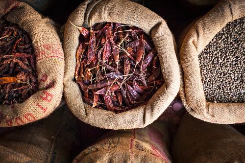 Getrocknete Chilischoten und Kichererbsen in Jutesäcken auf einem indischen Strassenmarkt