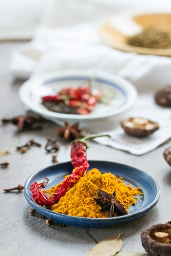 Turmeric powder, a dried chilli pepper, shiitake mushrooms and star anise on a table in front of a kitchen window