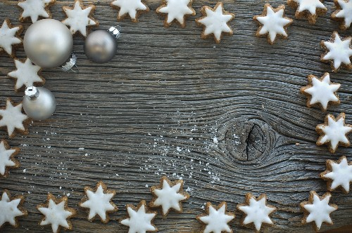 Cinnamon stars and Christmas tree baubles on a rustic wooden board