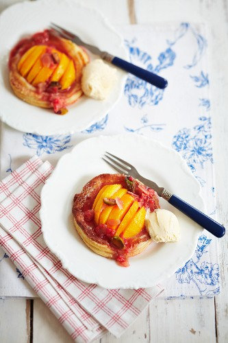 Peach puff pastry tart with raspberry sauce and ice cream