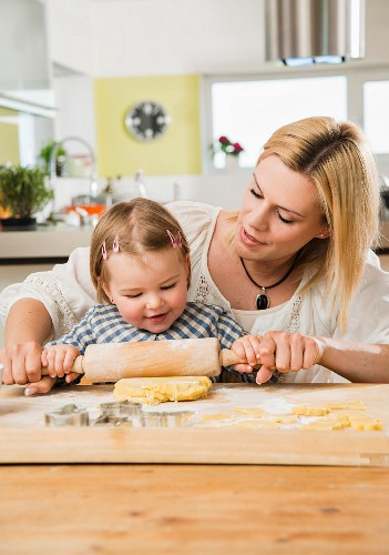 Mother and daughter with flour on nose baking in kitchen