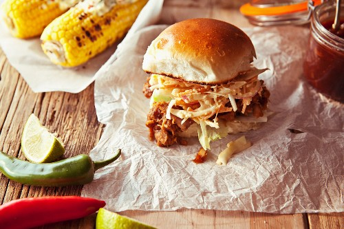 A pulled pork slider with apple coleslaw and grilled corn cobs (USA)