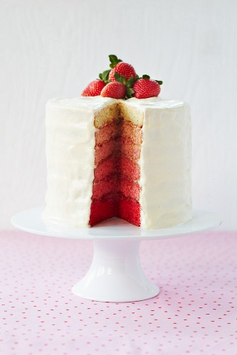 A six-layer sandwich cake with covered with white icing and strawberries, sliced