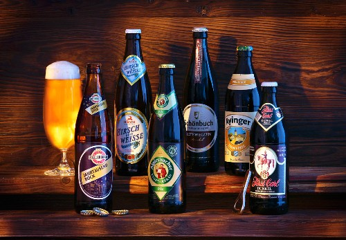 A glass of beer and various bottles of beer