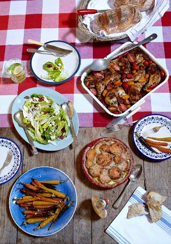A rustic table laid with herb chicken, sweet potato gratin and salad