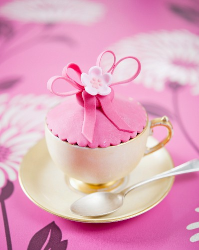 A pink flower cupcake in a cup