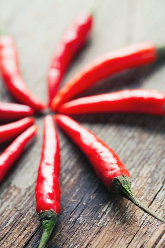 Bright red chilli peppers on a wooden surface