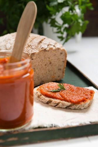 Ajvar (Paprikamus) im Glas und auf Brot